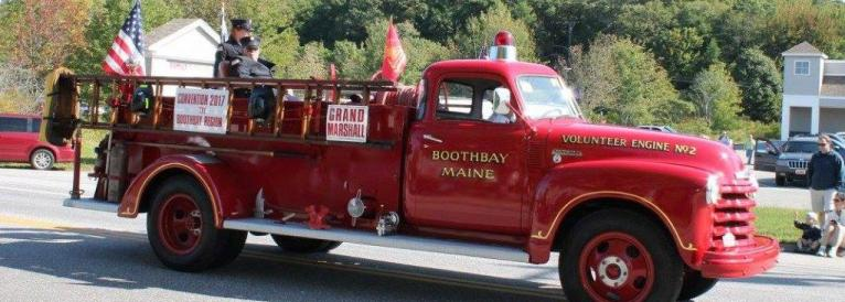 """Vntage fire truck with attached ladder drving slowly, with sign """"Grand Marshall"""" - 2 firefighters are riding in the open back"""